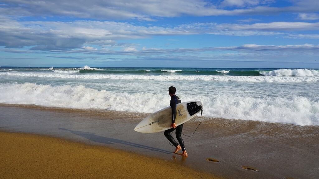 surfing in spain, man walking on the beach with surf gear