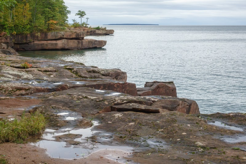 Sandstone outcroppings along shoreline of Big Bay State Park on Madeline Island, Wisconsin, USA, with puddles from occasional waves, on an overcast afternoon in autumn